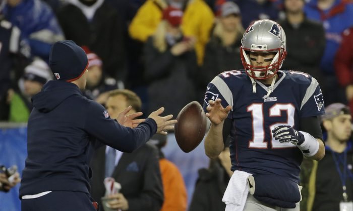 In this Sunday, Jan. 18, 2015, photo New England Patriots quarterback Tom Brady has a ball tossed to him during warmups before the NFL football AFC Championship game against the Indianapolis Colts in Foxborough, Mass. The NFL says its investigation into whether the New England Patriots used underinflated footballs in the AFC championship game is ongoing after a report Tuesday night. Jan. 20, 2015,  claimed the league found 11 balls were not properly inflated. (AP Photo/Matt Slocum, File)