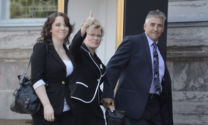 Conservative MP Shelley Glover (C) arrives with family members on Parliament Hill, July 15, 2013. Glover said at a Canada Council of the Arts reception on Jan. 20, 2015, that the arts are valuable in supporting freedom of expression. (The Canadian Press/Adrian Wyld)