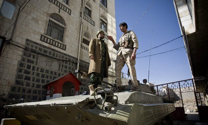 Houthi Shiite Yemeni wearing army uniforms stand atop an armored vehicle, which was seized from the army during recent clashes, outside the house of Yemen's President Abed Rabbo Mansour Hadi in Sanaa, Yemen, Thursday, Jan. 22, 2015. Heavily armed Shiite rebels remain stationed outside the Yemeni president's house and the palace in Sanaa, despite a deal calling for their immediate withdrawal to end a violent standoff. (AP Photo/Hani Mohammed)