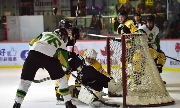 Darren Winia of the Macau Aces slots the puck into goal avoiding the clutching hand of Hong Kong Tycoons' King Ho in their CIHL match at Mega Ice on Saturday Jan 17, 2015. Aces won the contest with a massive 13-4 score line. (Bill Cox/Epoch Times)