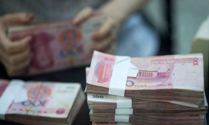 In this file photo, a worker counts currency in a bank in Shanghai, China. There have been a string of failures by private lending firms in China, leaving those who had invested their savings in the companies protesting to get their money back. (Johannes Eisele/AFP/Getty Images)
