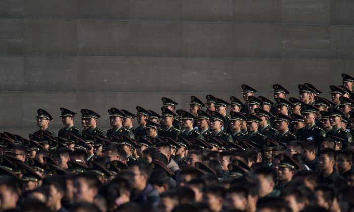 Soldiers of the People's Liberation Army (PLA) attend a memorial ceremony in Nanjing city, Jiangsu province on Dec. 13, 2014. A former office in the Chinese military recently revealed the rampant buying and selling of officer positions in the Chinese military, according to an overseas Chinese-language media. (Johannes Eisele/AFP/Getty Images)