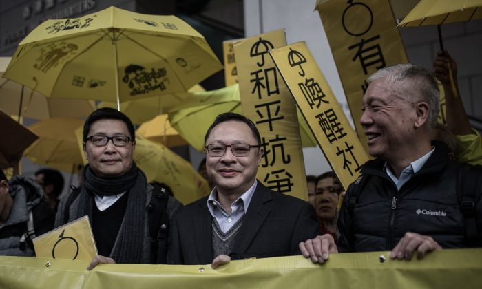Leading pro-democracy activists, Chan Kin-man (L), Benny Tai Yiu-ting (C) and Chu Yiu-ming hold a banner in front of the Wanchai police station in Hong Kong on Jan. 24, 2015. (Philippe Lopez/AFP/Getty Images)