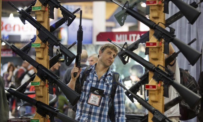 In this Jan. 17, 2013 file photo, Michael Kiefer of DeFuniak Springs, Fla., checking out a display of rifles at the Rock River Arms booth during the 35th annual SHOT Show in Las Vegas.  Nevada is one of several states considering allowing guns on college campuses. (AP Photo/Julie Jacobson)