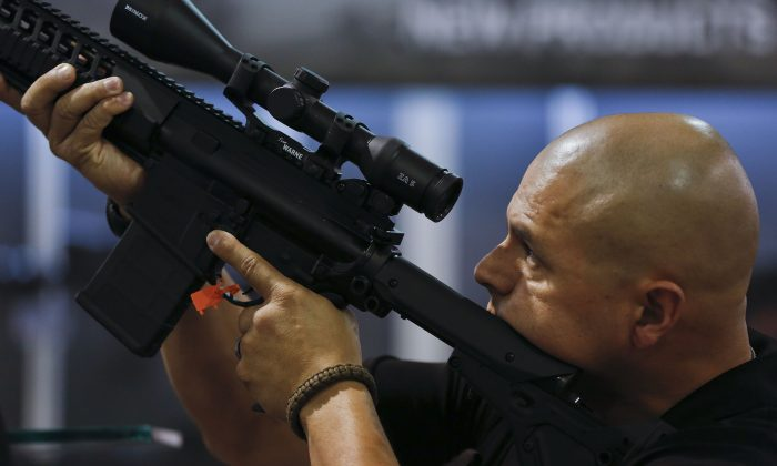 Michael Wright, of the Montgomery County Sheriff's office in Conroe, Texas, looking through the sight of a rifle at the Shooting Hunting and Outdoor Trade Show in Las Vegas, on Ja.14 2019. (AP Photo/Julie Jacobson)