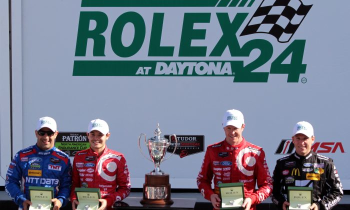 Tony Kanaan, Kyle Larson, Scott Dixon, and Jamie McMurray show off the Rolex watches and the trophy they earned by winning the Tudor United SportsCar Series Rolex 24 at Daytona. (Chris Jasurek/Epoch Times)