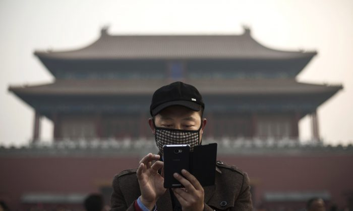 A man uses his smartphone on a hazy day outside the Forbidden City in Beijing on Nov. 20, 2014. (Kevin Frayer/Getty Images)