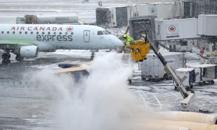 A plane is de-iced during a light snow at LaGuardia Airport in New York on Jan. 26, 2015. Airlines canceled thousands of flights into and out of East Coast airports as a major snowstorm packing up to three feet of snow barrels down on the region. (AP Photo/Seth Wenig)