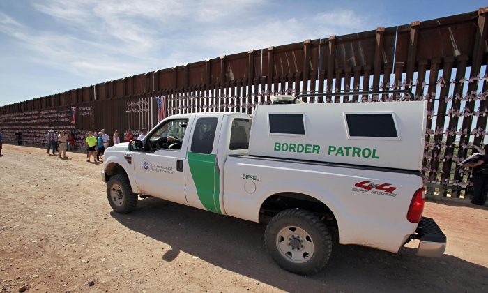 A U.S. Customs and Border Patrol agent patrols along the Arizona-Mexico border wall Sunday, Aug. 15, 2010 in Hereford, Ariz. (AP Photo/Matt York)