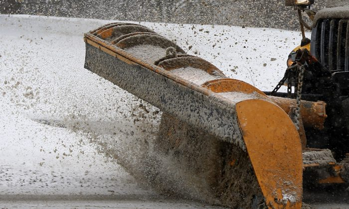 A Pennsylvania Department of Transportation truck plows snow from an overpass on Monday, Jan. 26, 2015, in Evans City, Pa. Over three inches of snow had already fallen and more is on the way as the storm moves across the northeast of the country. (AP Photo/Keith Srakocic)