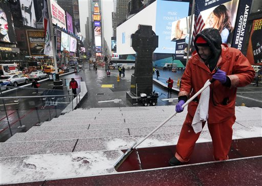 """Francisco Mathurine, of the Times Square Alliance, clears snow from the steps in Father Duffy Square in New York, Monday, Jan. 26, 2015. Officials cautioned Northeast residents to not be misled by a relatively smooth Monday morning commute, and pressed their cautions to prepare for a """"crippling and potentially historic"""" storm that could bury communities from northern New Jersey to southern Maine in up to 2 feet of snow starting later in the day. (AP Photo/Richard Drew)"""