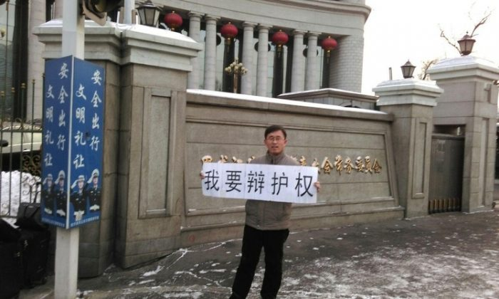 """Chinese lawyer Zhang Weiyu holds banner saying: """"I want to defend rights,"""" in front of the Heilongjiang provincial government on Jan. 20. The president of the Supreme People's Court in China has recently told judges to stop expelling lawyers from the court room. (Epoch Times)"""