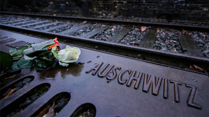 Roses left by mourners lie next to one of the many plaques detailing transports of Berlin Jews to concentration camps at the Gleis 17 (Track 17) in Berlin, Germany, on Jan. 27, 2015, the 70th anniversary of the liberation of Auschwitz. (Carsten Koall/Getty Images)