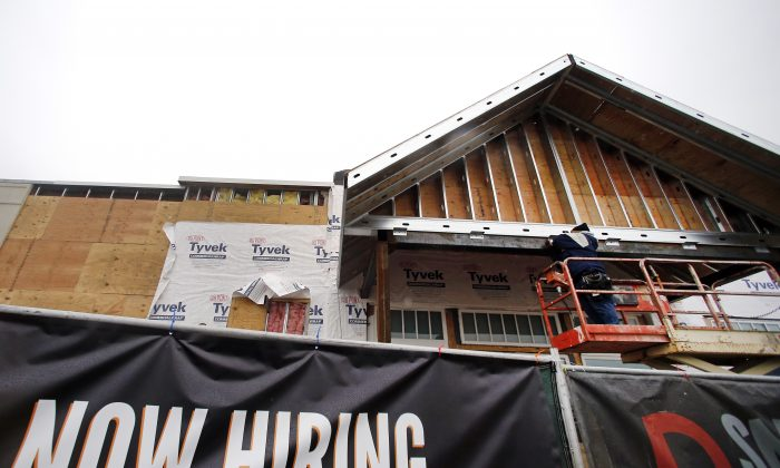 In this Jan. 12, 2015 file photo, a now hiring sign hangs nearby as a builder works on a commercial property under construction in Peabody, Mass.  (AP Photo/Elise Amendola, File)