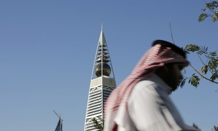A Saudi man passes the al-Faisaliya tower in Riyadh, Saudi Arabia, Tuesday, Jan. 27, 2015. President Barack Obama defended the U.S. government's willingness to cooperate closely with Saudi Arabia on national security despite deep concerns over human rights abuses, as he led an array of current and former American statesmen in paying respects Tuesday following the death of King Abdullah. (AP Photo/Hasan Jamali)