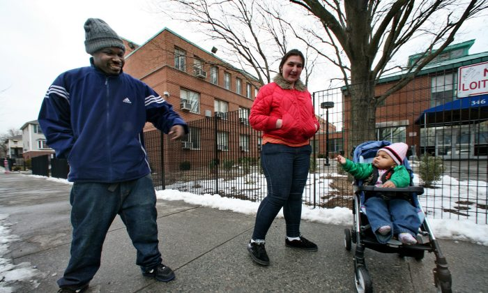 Mark and Galina Turner, and their son, Nareem, 18 months, arrive at the city's intake center for homeless families in the Bronx borough of New York, Friday March 6, 2009. The family expects help from the city to find a home after their recent eviction from an apartment, unable to pay rent from Galina's salary as a security guard. (AP Photo/Bebeto Matthews)