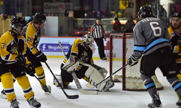Trapped by the boot........Hong Kong Tycoons' goalie Cody Drumm stops this attack during their CIHL match against South China Sharks at Mega Ice on Saturday Jan 24, 2015. Sharks went on to win the match in a tight 4-3 tussle and move within 2-points of the lead. (Bill Cox/Epoch Times)