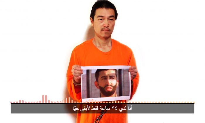 """This still image taken from a video posted on YouTube by jihadists on Tuesday, Jan. 27, 2015, purports to show a still photo of Japanese journalist Kenji Goto holding what appears to be a photo of Jordanian pilot 1st Lt. Mu'ath al-Kaseasbeh. Both are being held hostage by the Islamic State militant group. The still image was overdubbed with audio which condemns Jordan for not releasing Sajida al-Rishawi, saying that unless she is freed within 24 hours both will be killed. The Arabic subtitle reads """"I only have 24 hours left to live."""" The Associated Press could not independently verify the video. (AP Photo)"""