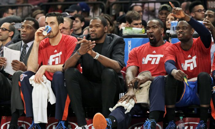 Oklahoma City Thunder forward Kevin Durant, center, cheers his team on during the first half of NBA basketball game against the New York Knicks, Wednesday, Jan. 28, 2015 at Madison Square Garden in New York.  (AP Photo/Mary Altaffer)