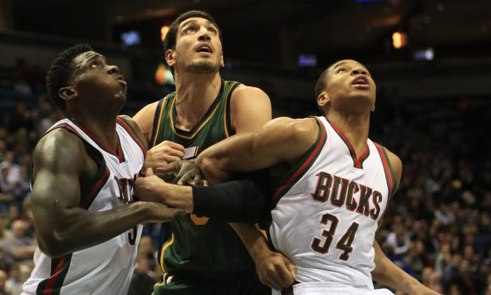 Utah Jazz center Enes Kanter, center, is defended by Milwaukee Bucks forward Johnny O'Bryant and Giannis Antetokounmpo, right, during the first half of an NBA basketball game Thursday, Jan. 22, 2015, in Milwaukee. (AP Photo/Darren Hauck)