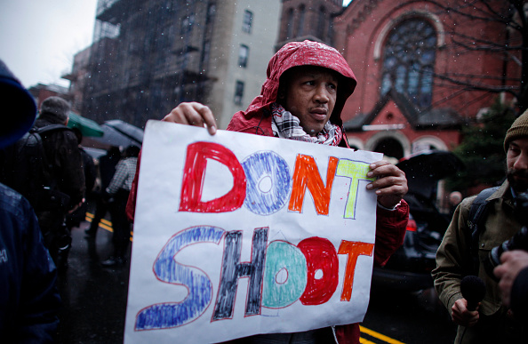 A Man holds a banner as he demand justice during the funeral service of Akai Gurley outside of the Brown Memorial Baptist Church on December 6, 2014. (Kena Betancur/Getty Images)