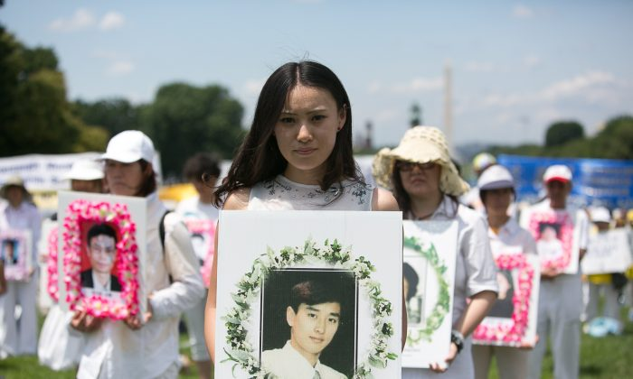 A young woman holds a poster during a rally in Washington on July 17, 2014, of Chinese man who was tortured to death for practicing Falun Gong inside China. (Edward Dai/Epoch Times)