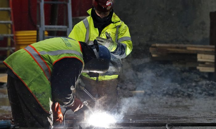 In this Monday, Jan. 12, 2015 photo, workers weld at a commercial construction site in Boston. (AP Photo/Elise Amendola)