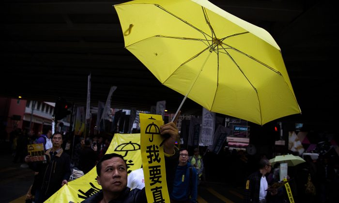 A man holds a yellow umbrella during tens of thousands of protesters march for the real universal suffrage on Feb. 1, 2015 in Hong Kong. (Lam Yik Fei/Getty Images)