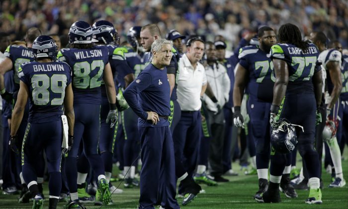 Seattle Seahawks head coach Pete Carroll, center, watches as players react after Russell Wilson was intercepted by New England Patriots strong safety Malcolm Butler during the second half of NFL Super Bowl XLIX football game Sunday, Feb. 1, 2015, in Glendale, Ariz. (AP Photo/Matt Rourke)