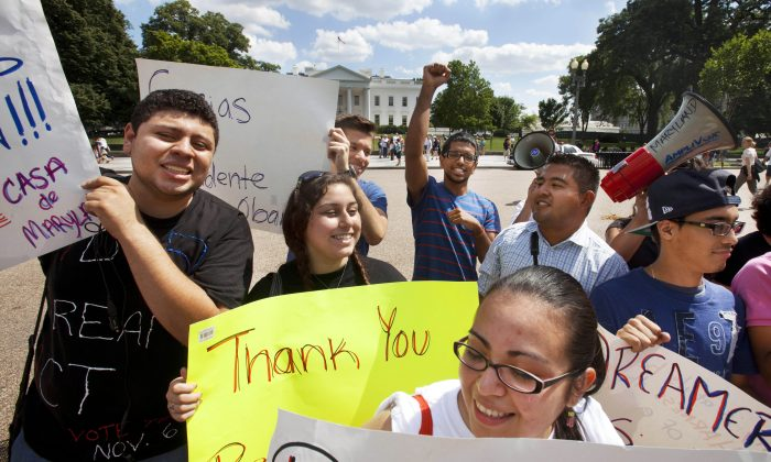 "In this June 15, 2012 file photo, Ricky Campos, 23, of Silver Spring, Md., left, Katye Hernandez, 22, both illegal immigrants originally from El Salvador, who live in Silver Spring, Md., hold signs saying ""Thank You President Obama"" in Washington, D.C. The group Casa de Maryland, rallied outside the White House in Washington in support of the president's announcement that the U.S. government will stop deporting and begin granting work permits to younger illegal immigrants who were brought to the U.S. by their parents when they were children, known as ""Dreamers."" Thousands of ""Dreamers"" are deciding if they will apply for DACA, or deferred action program, costing $465 dollars. Due to the price, some may wait for comprehensive immigration reform that might grant them legal residency. (AP Photo/Jacquelyn Martin, File)"