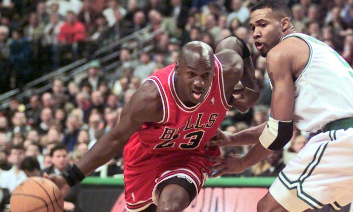 Chicago Bulls guard Michael Jordan (23) drives past Boston Celtics Ron Mercer (5) during an NBA basketball game in Boston on Oct. 31, 1997. (AP Photo/Stephan Savoia)