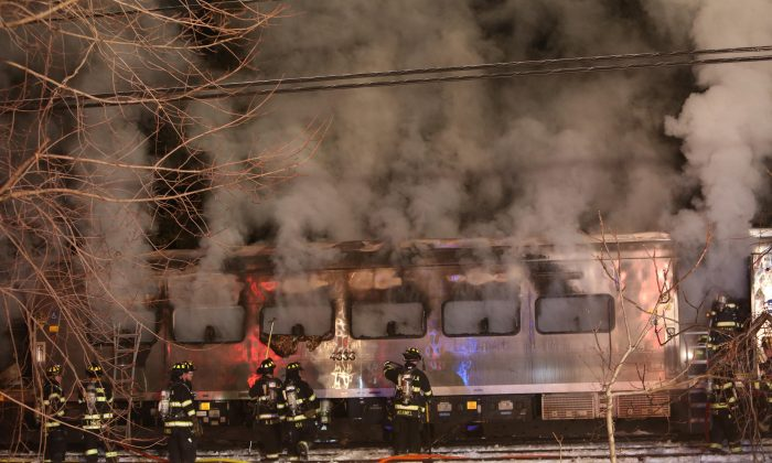 Firefighters work the scene of a collision between a Metro-North Railroad passenger train and two vehicles in Valhalla, N.Y., Tuesday, Feb. 3, 2015. (AP Photo/The Journal-News, Frank Becerra, Jr.)