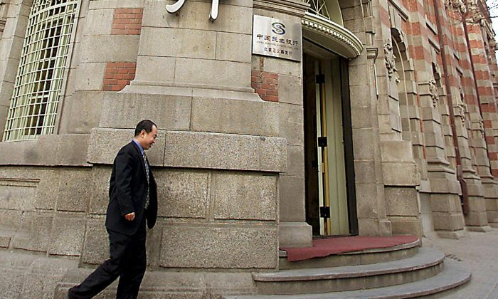 In this file photo, a man walks by the head office of China's largest private lender Minsheng Bank in Beijing, on Feb. 25, 2002. On Jan. 31, mainland Chinese media reported that the Mao Xiaofeng, the president of the bank, had been detained in a corruption investigation. (AFP/Getty Images)
