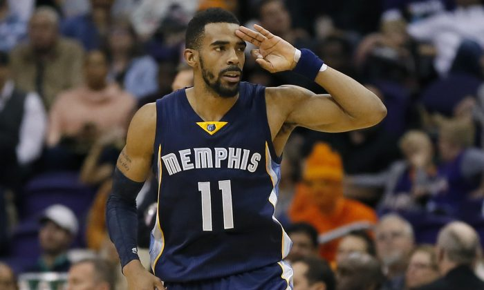 Memphis Grizzlies' Mike Conley (11) signals three after making a 3-pointer against the Phoenix Suns during the second half of an NBA basketball game, Monday, Feb. 2, 2015, in Phoenix. The Grizzlies won 102-101. (AP Photo/Matt York)
