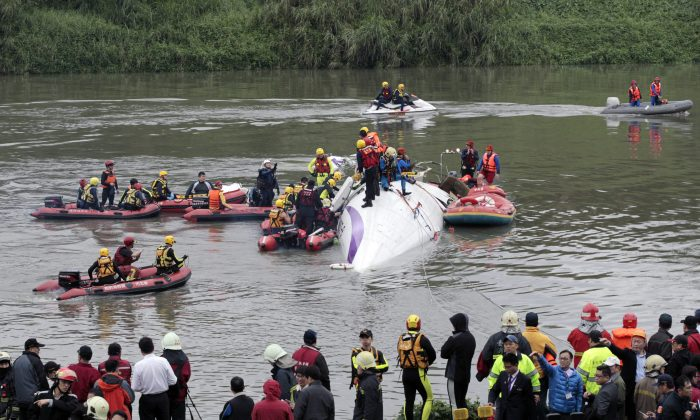 Emergency personnel try to extract passengers from a commercial plane after it crashed in Taipei, Taiwan, Wednesday, Feb. 4, 2015. (AP/Wally Santana)