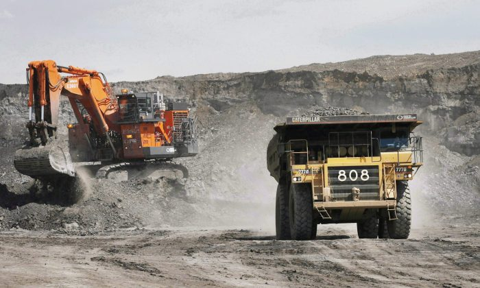 A haul truck carrying a full load drives away from a mining shovel at the Shell Albian Sands oil sands mine near Fort McMurray, Alta., on  July 9, 2008. (The Canadian Press/Jeff McIntosh)