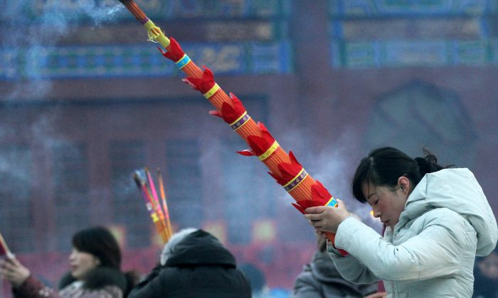 People light incense during the Laba Festival at Ciyunchansi Temple on Jan. 27, 2015 in Huai'an, Jiangsu Province, China. Enthusiasm for fortune telling and Feng Shui is common in Chinese communist officialdom as Party members lose faith in communism. (ChinaFotoPress/Getty Images)