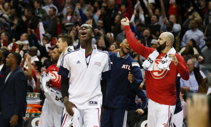 Atlanta Hawks guard Dennis Schroder, front, reacts after an Atlanta basket late in the second half of an NBA basketball game against the Portland Trail Blazers on Friday, Jan. 30, 2015, in Atlanta. Atlanta won 105-99 and stretched its winning streak to 18. (AP Photo/John Bazemore)