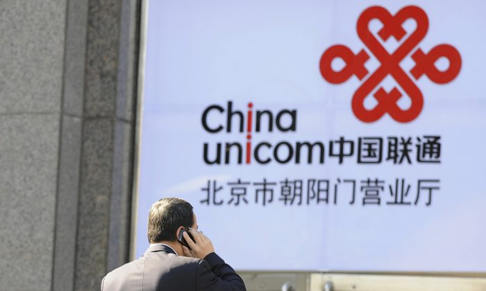 An office worker talks on a mobile phone in front of a China Unicom logo, California-based Apple's partner in China, in Beijing on Jan. 5, 2012. The Chinese regime's anti-corruption agency recently published a report concerning widespread corruption at the world's third-largest telecommunications provider. (Liu Jin/AFP/Getty Images)