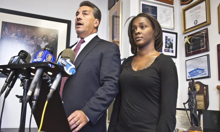 Attorney Scott Rynecki, left, and Kimberly Ballinger, the domestic partner of Akai Gurley and the mother of his toddler daughter, at a press conference on Thursday, Jan. 29, 2015, in New York City. The NYPD officer who shot and killed Gurley inside a Brooklyn housing project stairway has been indicted on charges of manslaughter.  (AP Photo/Bebeto Matthews)