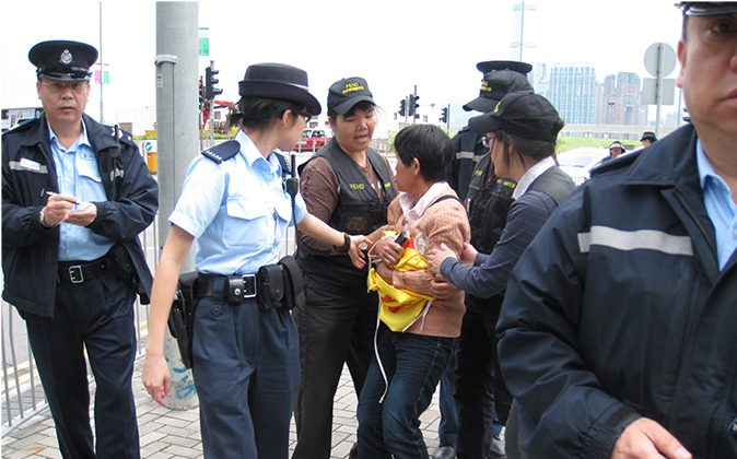 Food and Environmental Hygiene Department officers are attempting to take away a Falun Gong banner held by a practitioner Ms Poon (center) on May 2, 2013. (Epoch Times)
