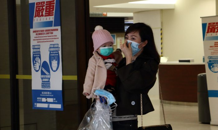 A woman holds a child while putting on a mask at Queen Mary Hospital on Feb. 5. (Kiri Choi/Epoch Times)