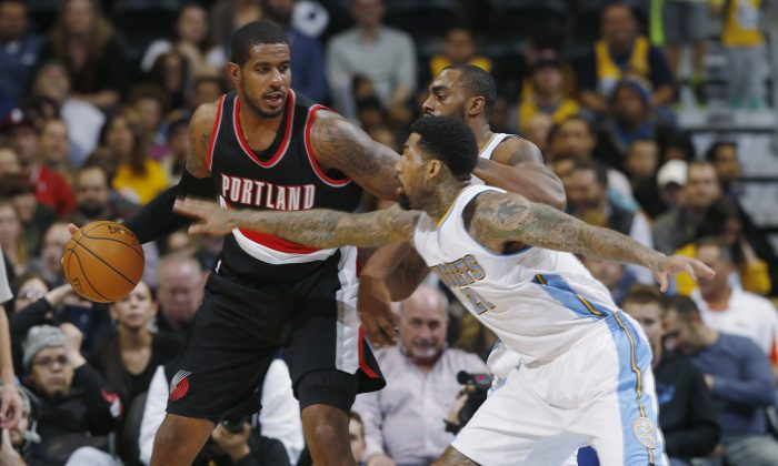 Portland Trail Blazers forward LaMarcus Aldridge, left, fends off defensive efforts of Denver Nuggets forward Wilson Chandler, front right, and guard Arron Afflalo in the third quarter of the Trail Blazers' 105-103 victory in an NBA basketball game in Denver on Tuesday, Dec. 2, 2014. (AP Photo/David Zalubowski)