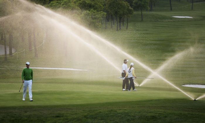 Adam Blyth (L) and Clay Deverslook look on as the sprinkler goes off on the 9th green before the group finishes play during the round one of the BMW Asian Open 2006 at Tomson Golf Club in Shanghai, China. (Cancan Chu/Getty Images)