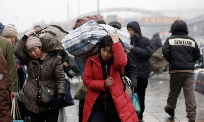 "Migrant workers arrive at the Beijing Railway Station with their luggage on January 31, 2013 in Beijing, China. The Ministry of Public Security, an agency with the State Council, announced a plan to scrap the ""temporary"" residence permit in China. (Lintao Zhang/Getty Images)"