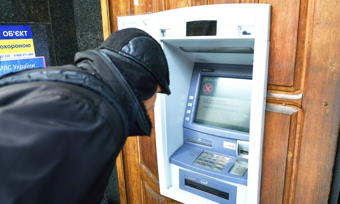 A man stands in front an ATM machine which is out of order, on November 26, 2014 in the eastern Ukrainian city of Donetsk. (ERIC FEFERBERG/AFP/Getty Images)