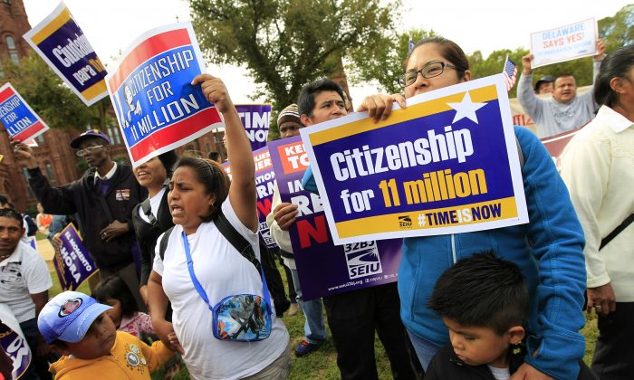 Demonstrators hold up their banners during a immigration a rally on the National Mall in Washington, Tuesday, Oct. 8, 2013, calling on the House Republican leadership to pass comprehensive immigration reform with a path to citizenship. ( AP Photo/Jose Luis Magana)