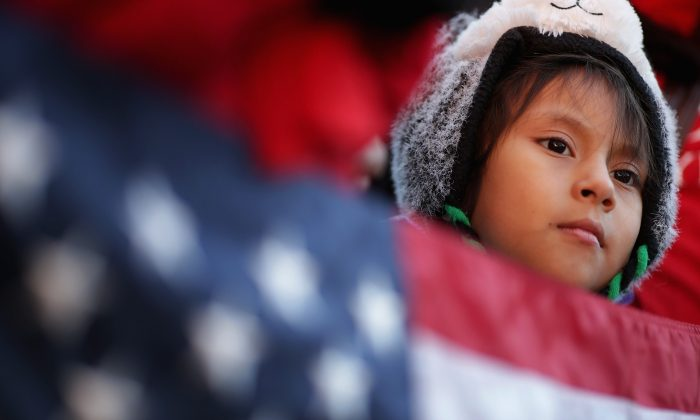 A little girl holds the American flag during a rally in support of President Barack Obama's executive action on immigration policy in Washington on Nov. 21, 2014. (Chip Somodevilla/Getty Images)