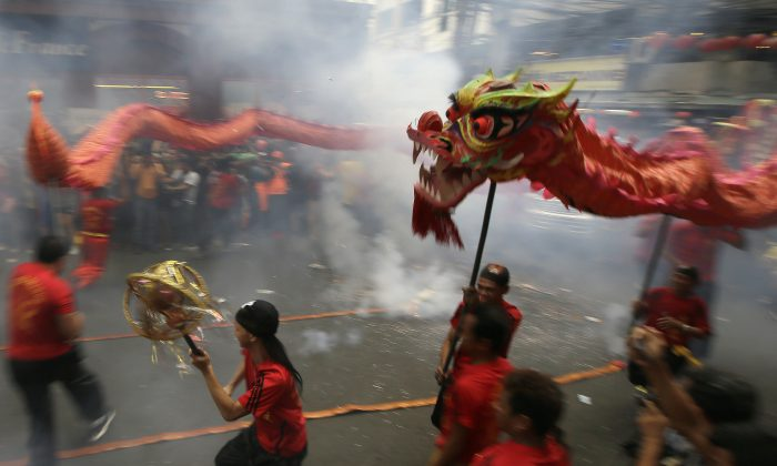 """Dragon dancers perform in front of a supermarket at Manila's Chinatown district of Binondo to celebrate the Chinese New Year Thursday, Feb. 19, 2015 in Manila, Philippines. This year marks the """"Year of the Sheep"""" in the Chinese Lunar calendar. (AP Photo/Bullit Marquez)"""