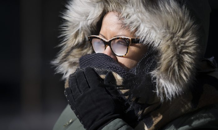 Pedestrians brave the cold during their morning commute, Friday, Feb. 20, 2015, in New York. Arctic air and bitterly cold wind is moving across the Northeast, plunging temperatures into record low single digits, accompanied by subzero wind chills. (AP Photo/John Minchillo)